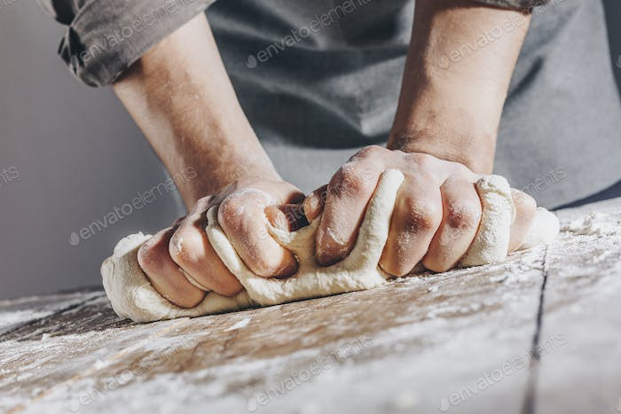 Chef making and kneading fresh dough