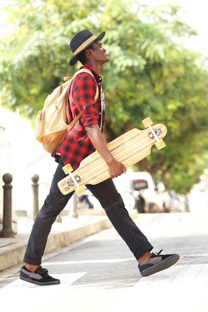 Side portrait of cool young african guy in hat walking outdoors with skateboard and bag