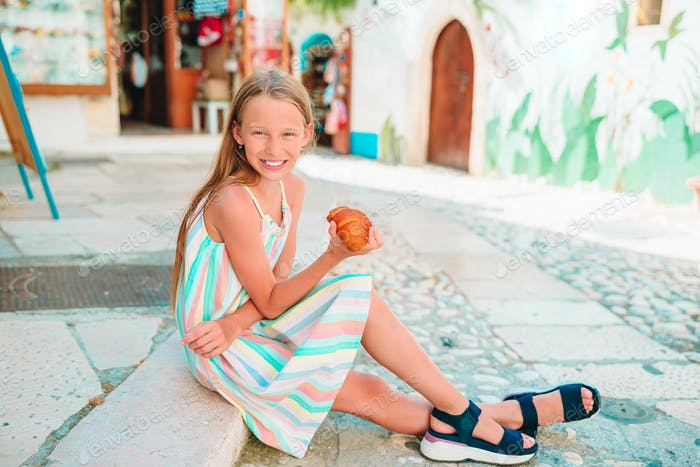 Little girl eats croissant on old streets in european village