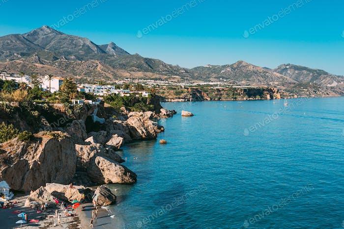 Nerja In Spain. People Resting On Beach Calahonda, Coast Near Resort Town Of Nerja In Spain
