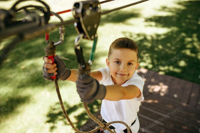 Little boy climbs in rope park, top view