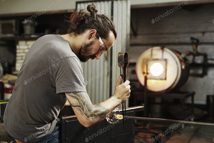 A glassblower with pliers working on a piece of glass.