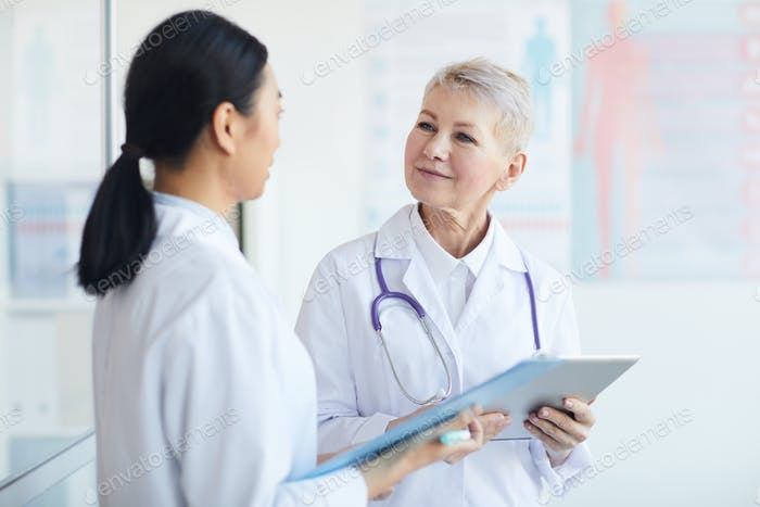 Mature Female Doctor Talking to Intern in Clinic