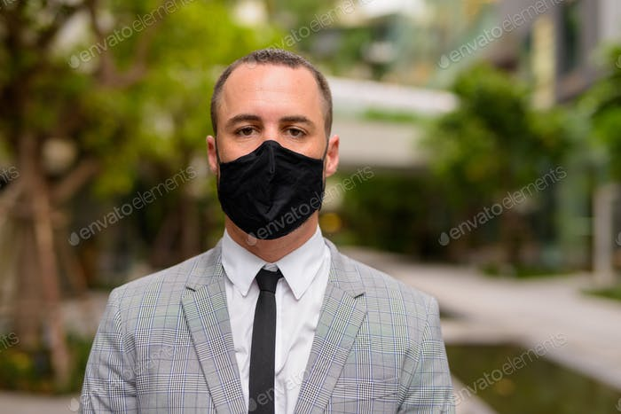 Face of Hispanic bald businessman wearing mask for protection from corona virus outbreak in the city