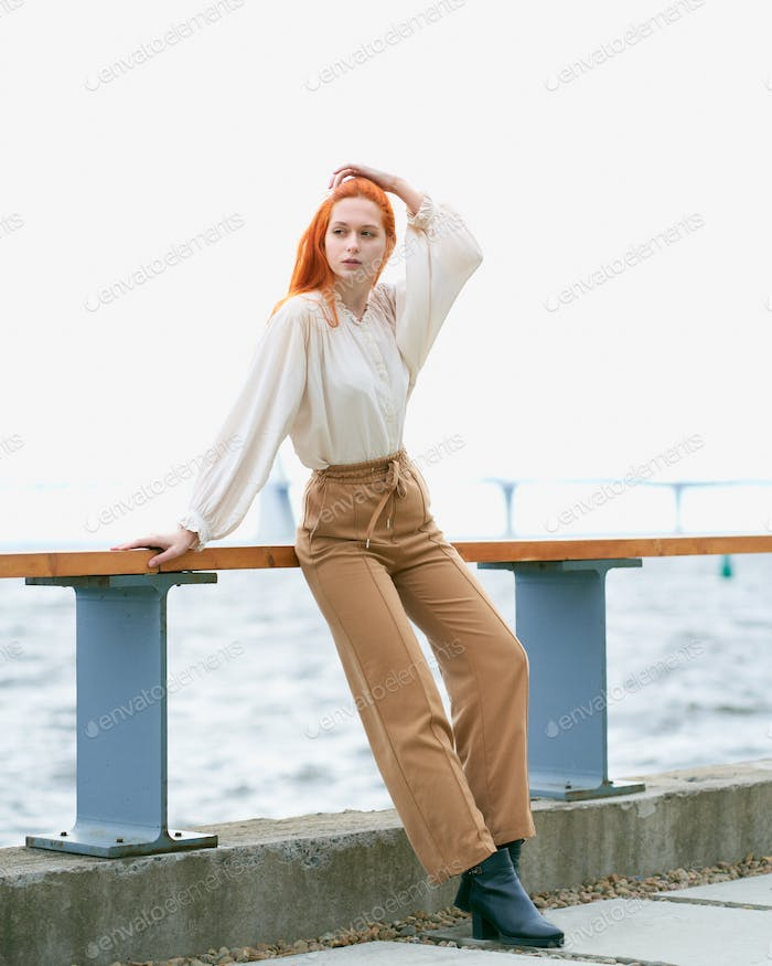 Full length redhead female in casual clothes posing on pier