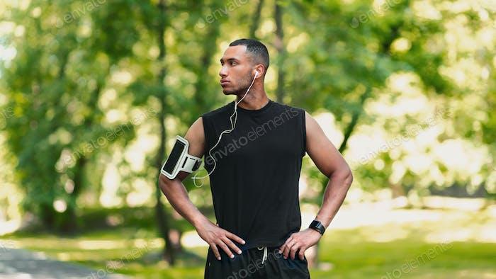 Schöner Afroamerikaner Athlet mit Ohrhörern Musik hören während seiner Pause im Park
