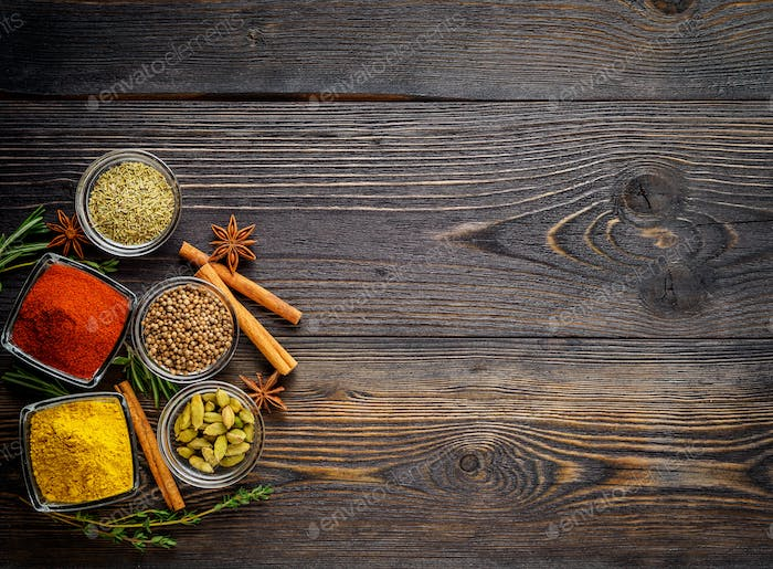 Set of spices and herbs on dark brown textured wooden table. Top view, empty space