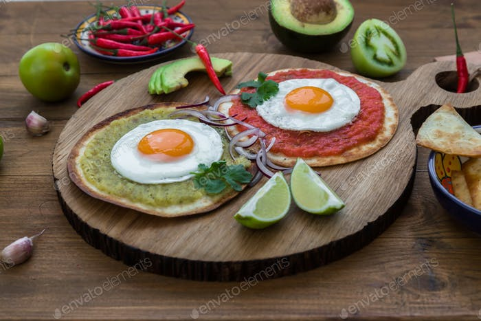 Huevos divorciados, delicious food with eggs, fresh salad and herbs  spicy  herby sauce