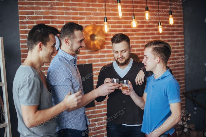 Cheerful old friends communicate with each other  glasses of whiskey in pub