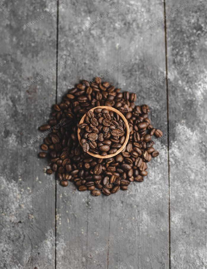 coffee beans in wood saucer with grunge black background