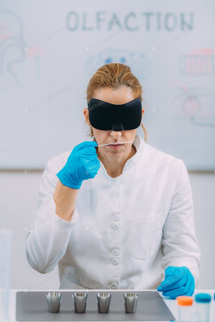 Olfaction. Female Scientist Examining Smells with Mask.