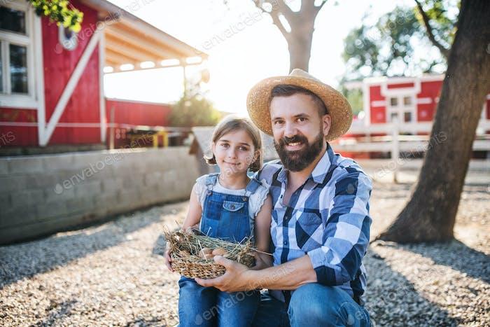 Ein Vater mit kleiner Tochter im Freien auf Familienfarm, hält Eier
