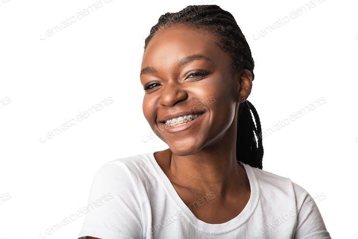 Afrikanische Frau mit Zahnspangen lächelnd posiert über weißem Hintergrund