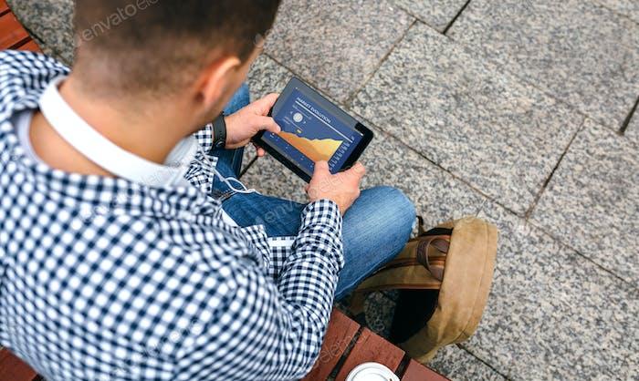 Unrecognizable man looking cryptocurrencies in tablet
