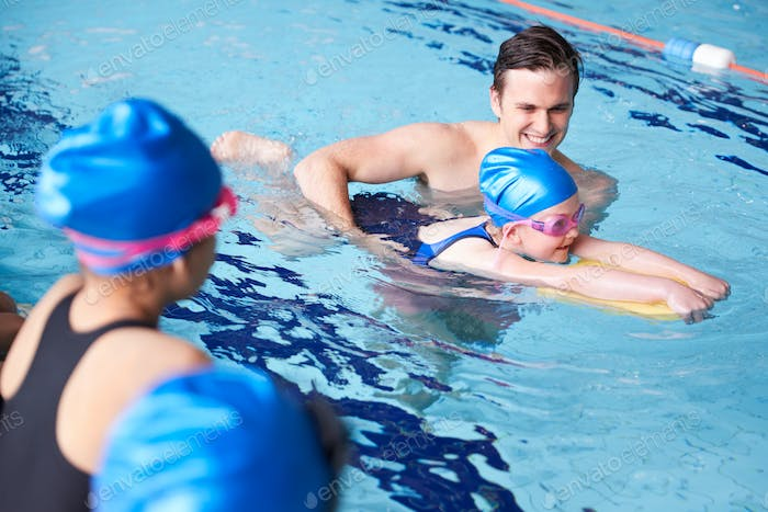 Male Coach In Water Giving Group Of Children Swimming Lesson In Indoor Pool
