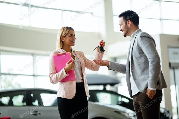 Professional salesperson during work with customer at car dealership. Giving keys to new car owner