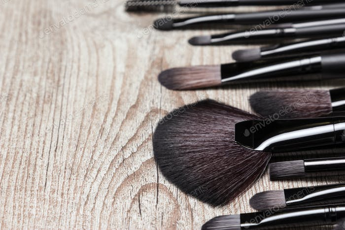 Various makeup brushes on shabby wooden surface