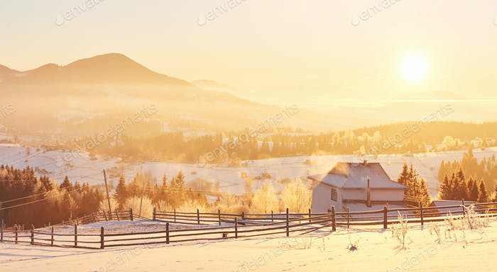 The mysterious winter landscape is majestic mountains in winter. Fantastic sunset. Recording houses