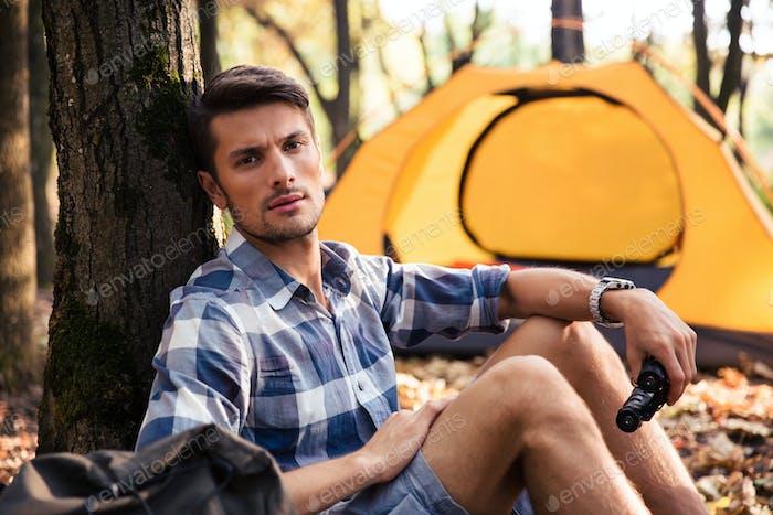 Mann ruht in der Nähe von Zelt im Wald
