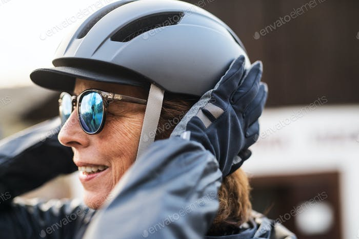Close-up of active senior woman standing outdoors, putting on bicycle helmet.