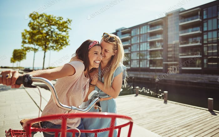 Laughing female friends walking with a bicycle through the city