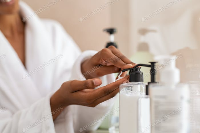 Woman taking body moisturizer from dispenser