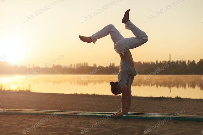 Athletic yoga man workout training on the beach sunrise