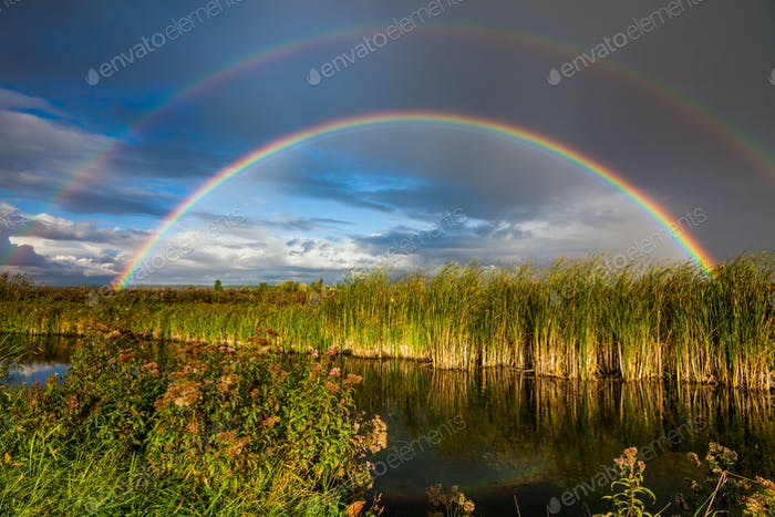 Amazing double rainbow over the small rural river.