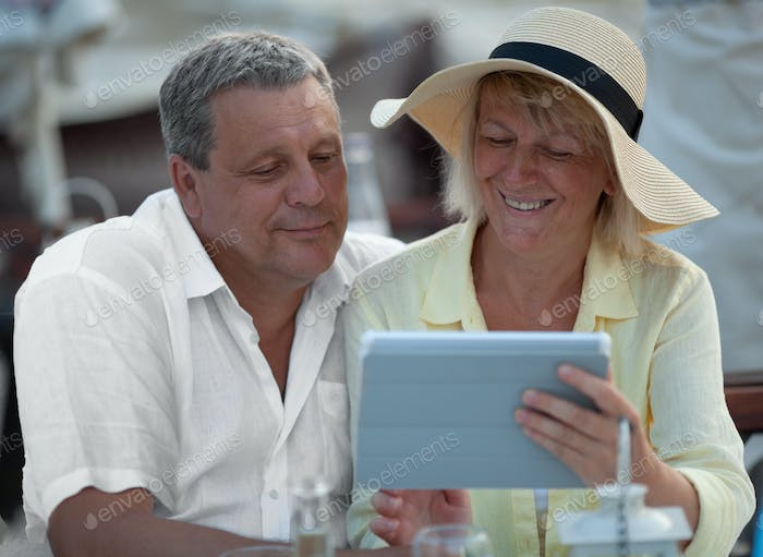 Cheerful mature couple with touch pad outdoor