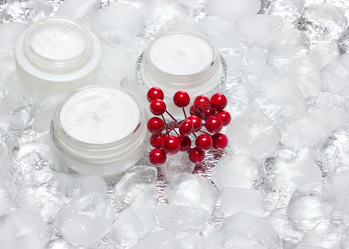 Glass jars of cream with red berries bunch surrounded by ice cub