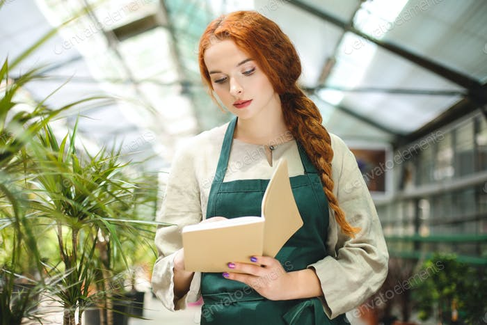 Beautiful florist in apron standing and thoughtfully making notes in notepad working in greenhouse