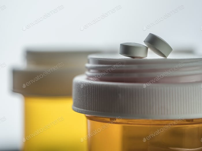 Two white pills on a boat of medicines of plastic color amber, conceptual image