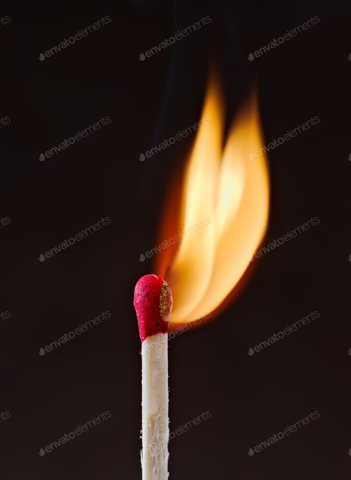 match flame the moment it is lit in front of dark background