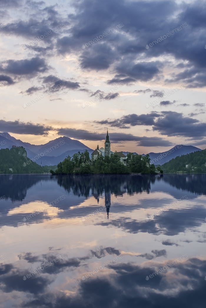 Village church and buildings reflected in still lake, Bled, Upper Carniola, Slovenia