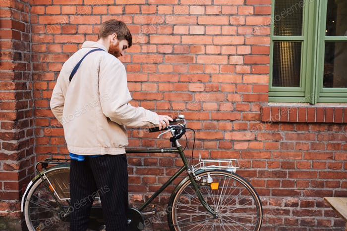 Back view of young man parking his bicycle near brick wall outdoor