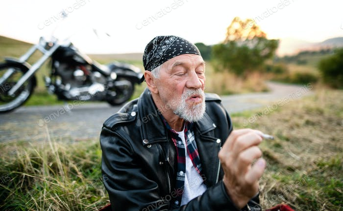 A cheerful senior man traveller with motorbike in countryside, smoking.