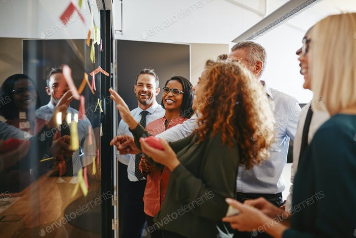 Diverse businesspeople laughing while brainstorming together with sticky notes