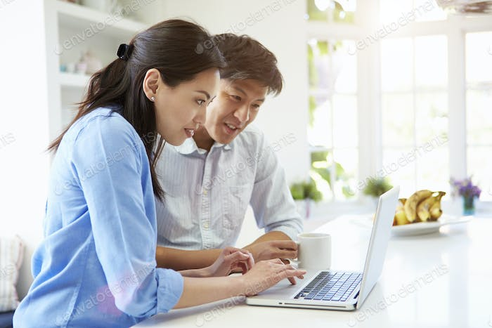 Asian Couple Looking at Laptop In Kitchen