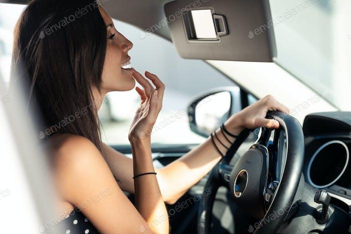Schöne junge Frau trägt Lippenbalsam auf, während sie im Rückspiegel im Auto schaut.