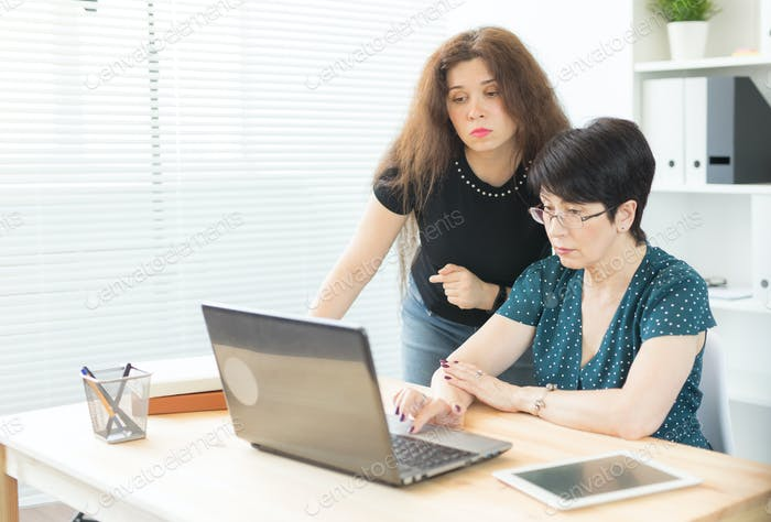 People, technology and communication concept - Young woman help her colleague with a laptop