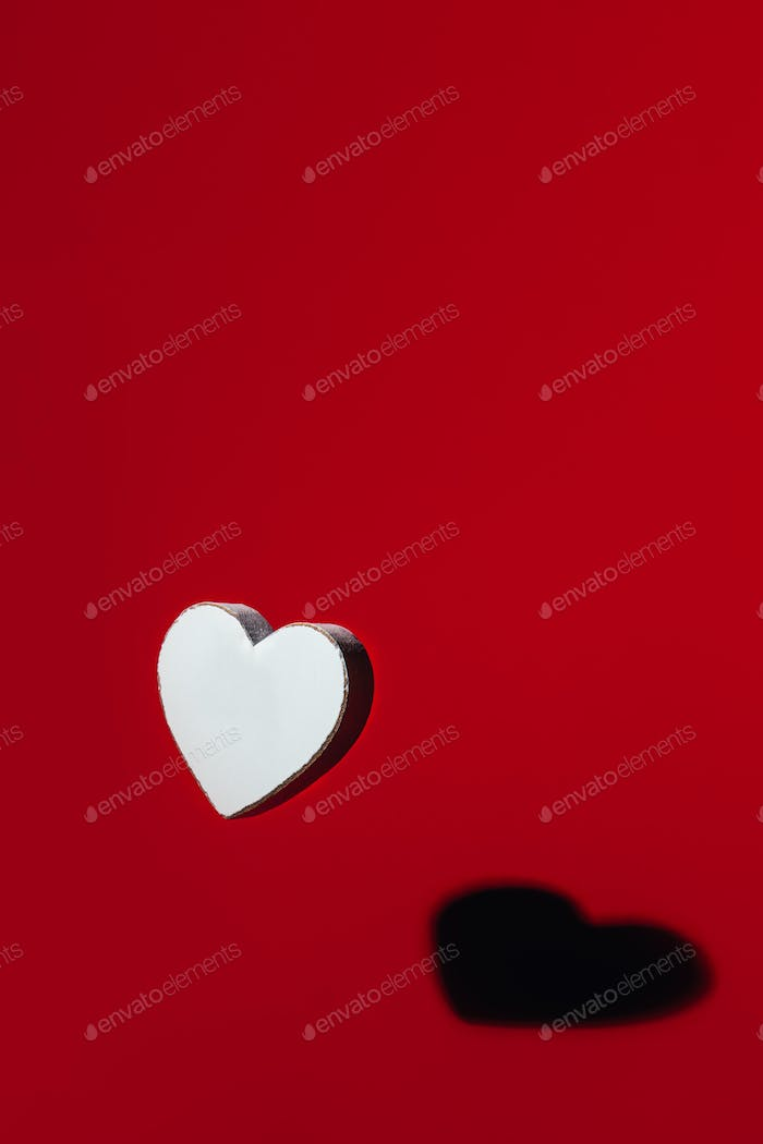 White wooden heart with strong shadow