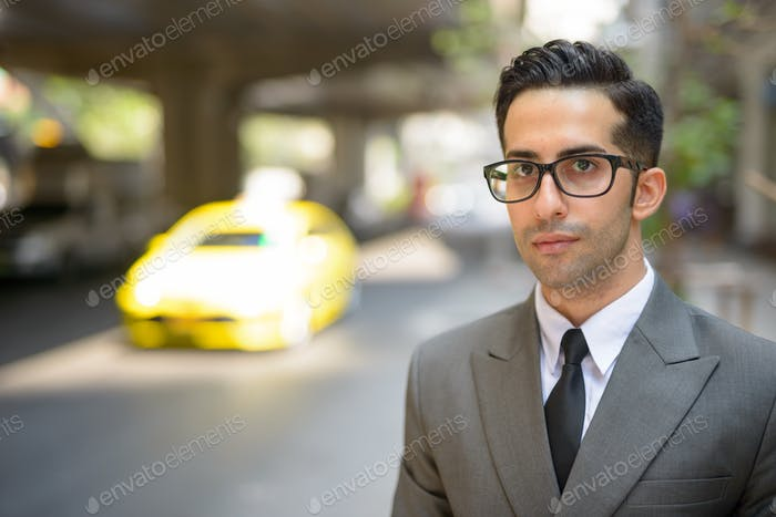 Face of young handsome Persian businessman thinking in the city streets outdoors