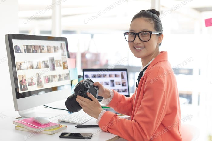 Asian female graphic designer looking at camera while working at desk