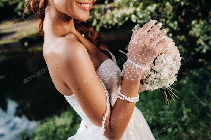 portrait of an elegant bride in a white dress with a bouquet in nature in a nature Park.Model in a