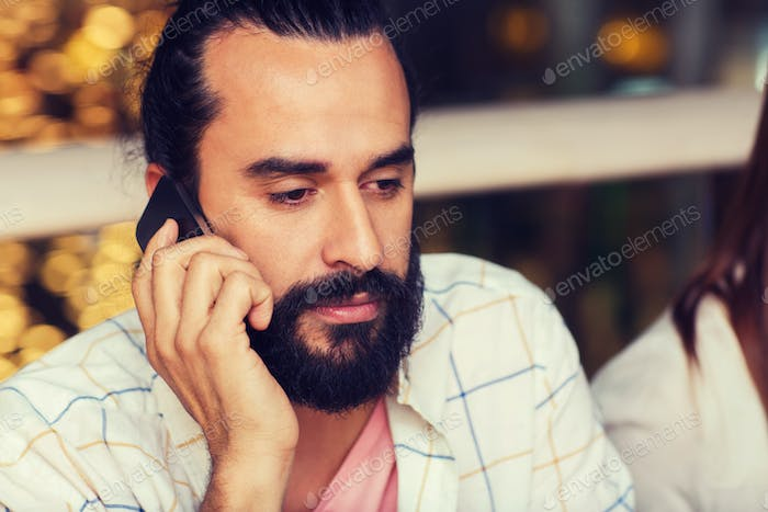 sad man calling on smartphone at restaurant