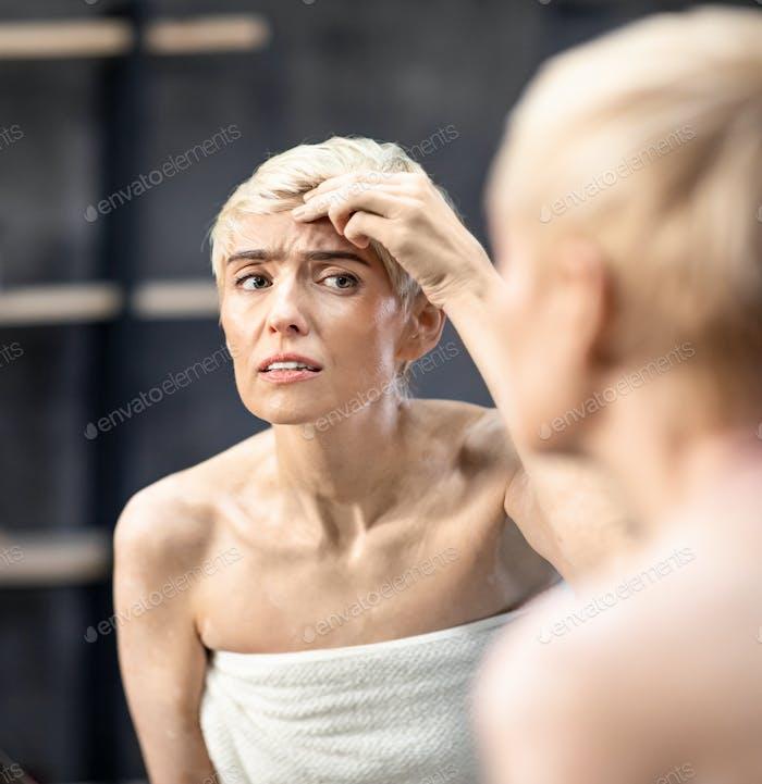 Concerned Lady Looking At Wrinkles Standing In Bathroom Indoor