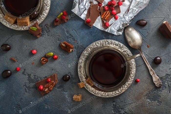 Cups of coffee with chocolate on a stone background.
