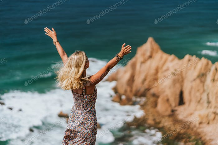 Beautiful women raising hands enjoying ocean breeze on impressive Praia da Ursa Beach in morning