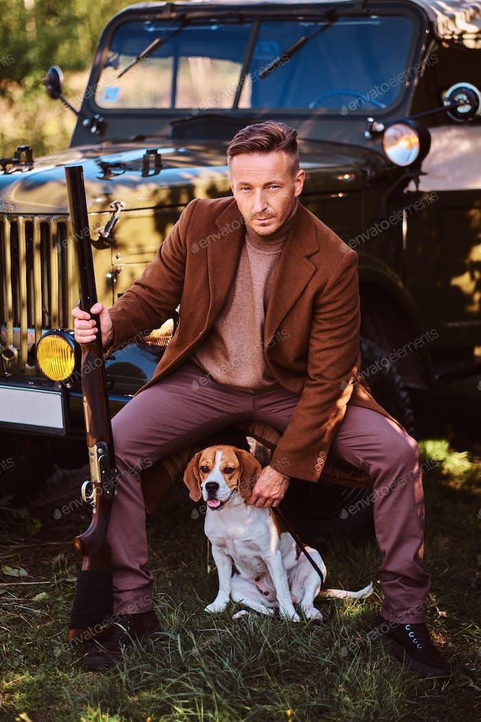 Jäger in eleganter Kleidung zusammen mit seinem Beagle-Hund neben einem Retro-Militärauto im Wald.