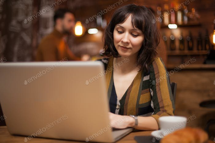 Young confident woman wokring on her laptop in a coffee shop